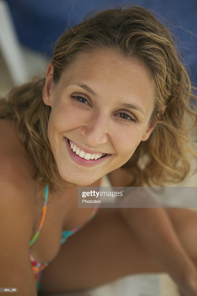 portrait of a young Caucasian woman in a bikini as she turns and smiles while vacationing : Foto de stock