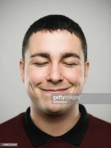 portrait of a young caucassian man closing eyes and smiling - eyes closed stock pictures, royalty-free photos & images