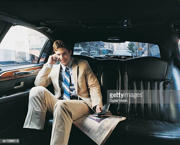 Portrait of a Young CEO Sitting in the Back Seat of a Car Using a Mobile Phone and a Handheld PC