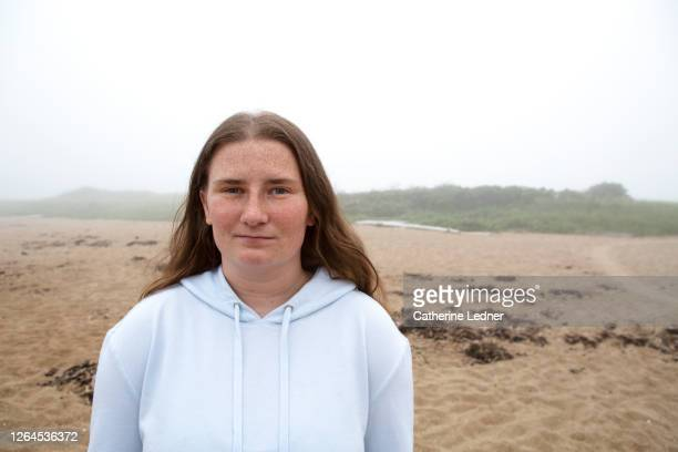 portrait of a young college student with long hair and freckles at the beach on a foggy day in maine - catherine ledner stock pictures, royalty-free photos & images
