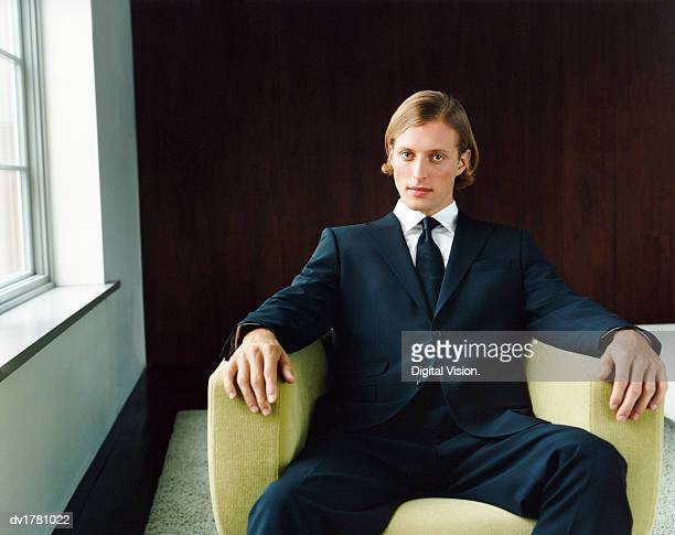 portrait of a young, confident man in a black suit sitting in an armchair by a window - metrosexual stock pictures, royalty-free photos & images