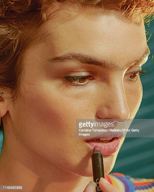 portrait of a young confident woman applying lipliner - lip liner stock photos and pictures