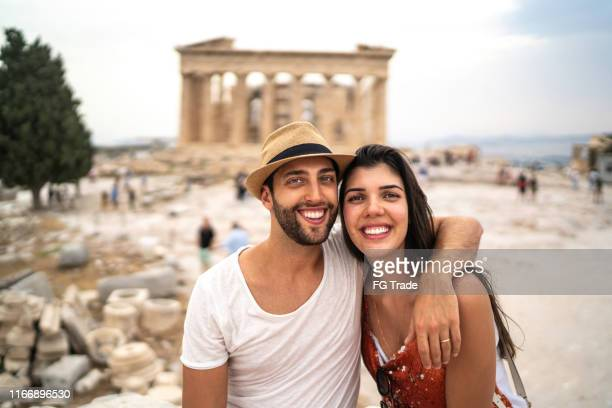 portrait of a young couple embracing in front of the parthenon, athens - parthenon athens stock pictures, royalty-free photos & images