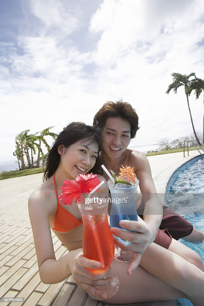 Portrait of a Young Couple Holding Cocktails by the Poolside : Stock Photo