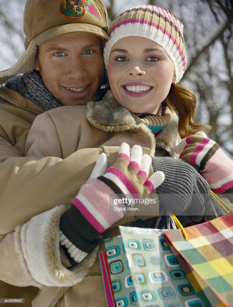 Portrait of a Young Couple in Winter Outfits Holding Shopping Bags and Embracing : Stock Photo