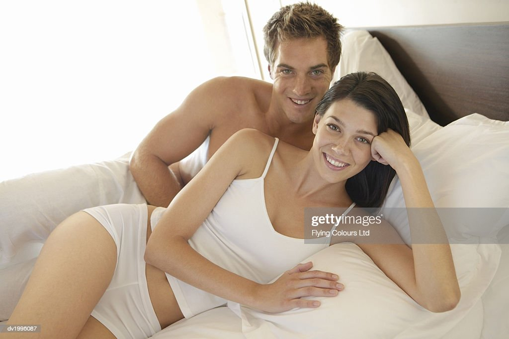 Portrait of a Young Couple Lying on a Bed in Their Underwear : Stock Photo