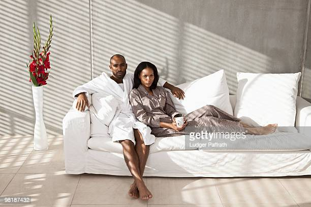 portrait of a young couple on a sofa - barefoot black men stock pictures, royalty-free photos & images