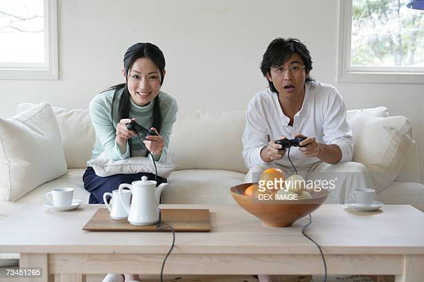 Portrait of a young couple sitting on a couch and playing video games