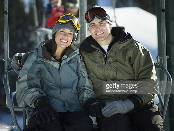 Portrait of a young couple sitting on a ski lift