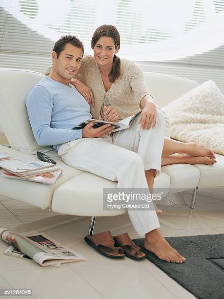 Portrait of a Young Couple Sitting on a Sofa With Magazines in Their Sitting Room