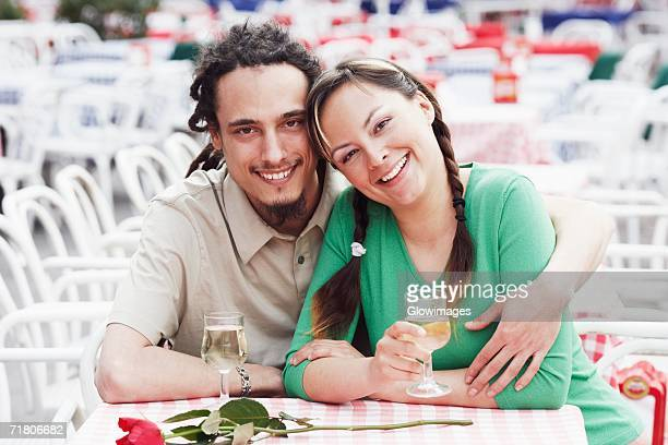 Portrait of a young couple sitting together at a sidewalk cafe