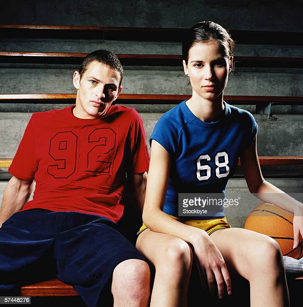 portrait of a young couple sitting with a basketball