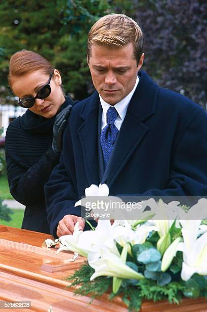 portrait of a young couple standing over a coffin