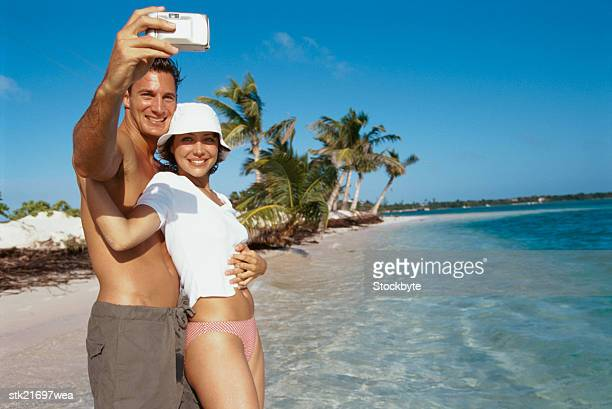 portrait of a young couple taking a photograph of themselves at the beach