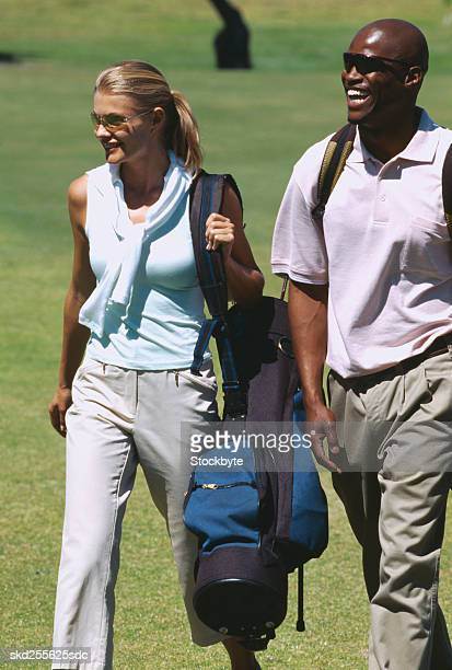 Portrait of a young couple walking on a course with golf bags