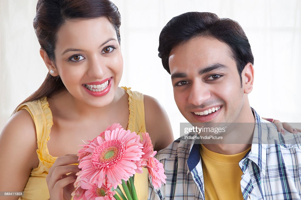 Portrait of a young couple with flowers : Stock Photo