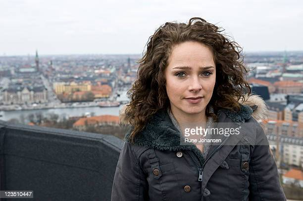 Portrait of a young Danish woman, 26 years old, outdoors in a charcoal colored coat, with views of Copenhagen, Denmark in the background