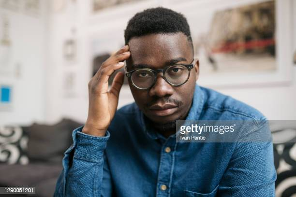 portrait of a young depressed african american man sitting at home - uncertainty stock pictures, royalty-free photos & images