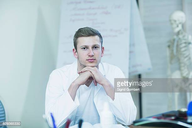 portrait of a young doctor sitting in his office and skeleton in the background, freiburg im breisgau, baden-w��rttemberg, germany - sigrid gombert imagens e fotografias de stock
