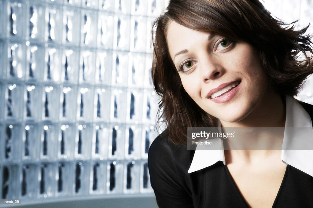 portrait of a young exotic looking business woman in a black blouse as she smiles brightly : Stockfoto