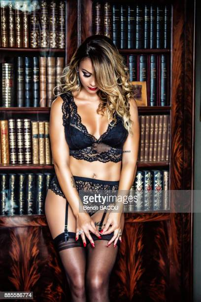 portrait of a young face of woman in black lingerie, looking down, clinging a suspender belt to a library - stockings and suspenders - fotografias e filmes do acervo