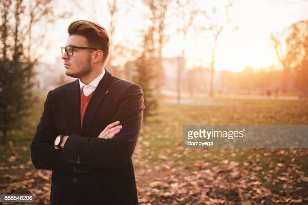 Portrait of a young fashionable man in the public park