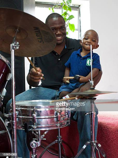 Portrait of a young father with his son playing the drums at the sunday service in the Zion Baptist Church in Old Bight on June 15 2012 in Cat Island...