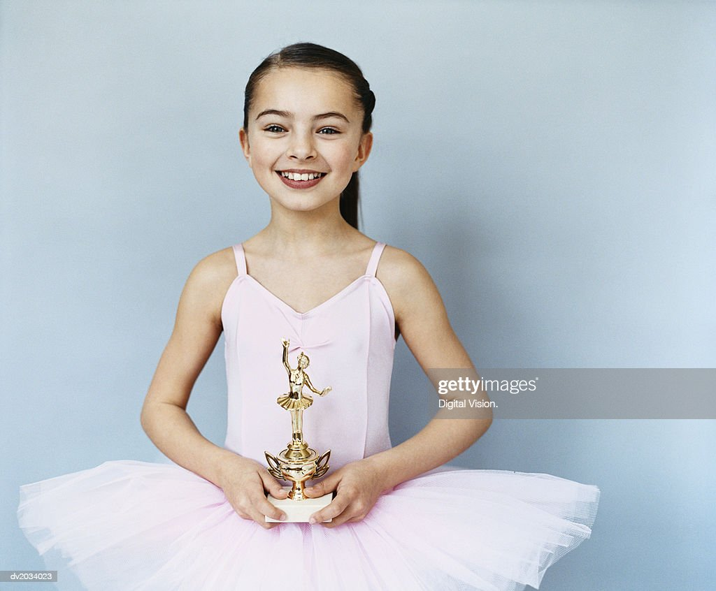 Portrait of a Young, Female Ballet Dancer Holding a Trophy : Stock Photo