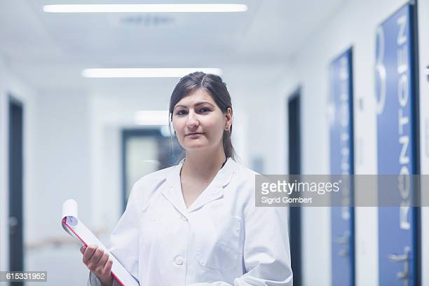 portrait of a young female doctor holding clipboard in hospital corridor, freiburg im breisgau, baden-württemberg, germany - sigrid gombert 個照片及圖片檔