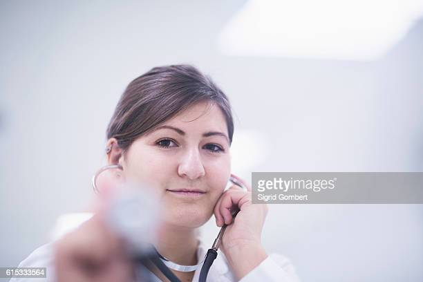 portrait of a young female doctor listening heart beat from stethoscope, freiburg im breisgau, baden-württemberg, germany - sigrid gombert stock pictures, royalty-free photos & images