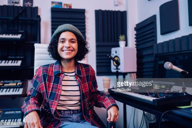 portrait of a young female musician at her workplace in the recording studio - singer songwriter stock pictures, royalty-free photos & images