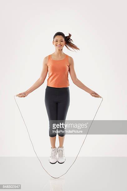 Portrait of a young fit woman skipping over white background