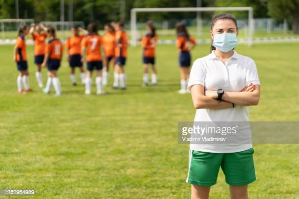 科維德-19。一名年輕足球教練因冠狀病毒大流行而戴著面罩的肖像。 - 足球 團體運動 個照片及圖片檔