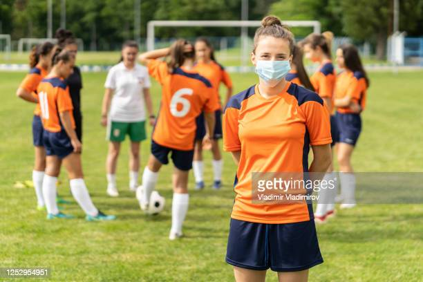 covid-19. portrait of a young football player wearing face mask due to coronavirus pandemic. - sporting term stock pictures, royalty-free photos & images