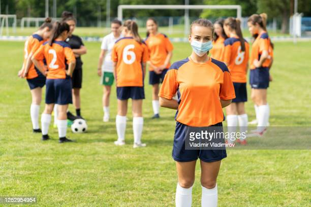 covid-19. portrait of a young football player wearing face mask due to coronavirus pandemic. - football face mask stock pictures, royalty-free photos & images