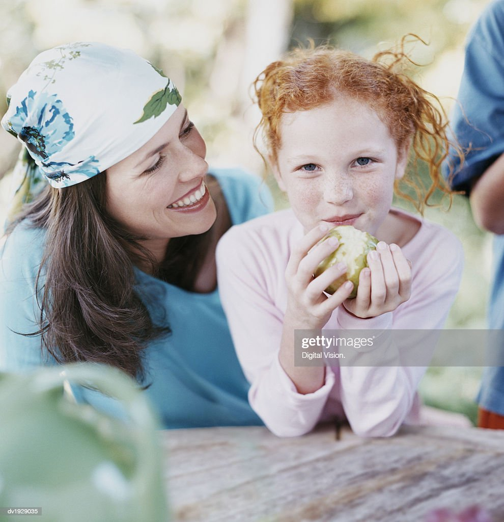 Portrait of a Young Girl and Her Mother, Girl Eating an Apple : Stock Photo