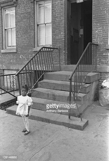 Portrait of a young girl as she poses in front of an apartment building's stoop on an unidentifed Harlem street New York 1972 Behind her graffiti...
