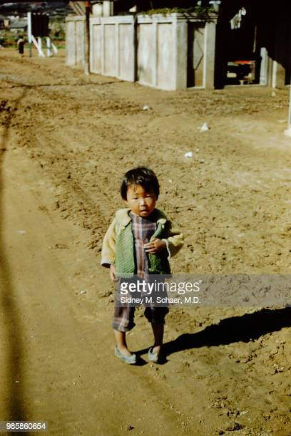 Portrait of a young girl as she stands on a dirt road Inchon South Korea January 1952