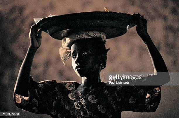 Portrait of a young girl carrying snacks and fish for sale in a Mali market.