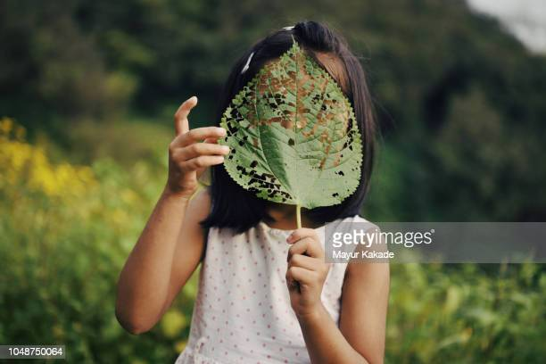 Portrait of a young girl covering her face with leaf