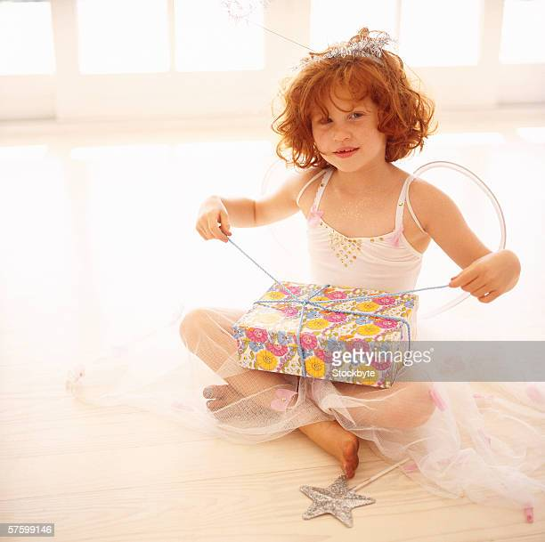 portrait of a young girl (6-8) dressed in an angels costume and opening a gift