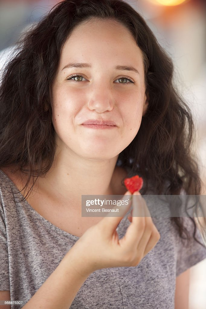 Portrait of a young girl eating a strawberry : Stock Photo