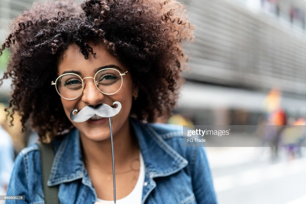 Portrait of a Young Girl Having Fun with Mustache : Stock Photo