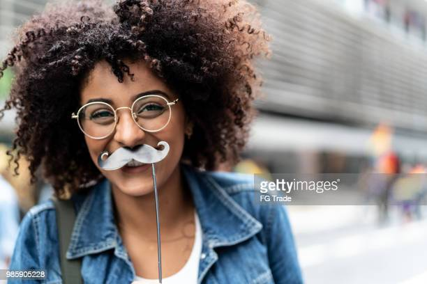 Portrait of a Young Girl Having Fun with Mustache