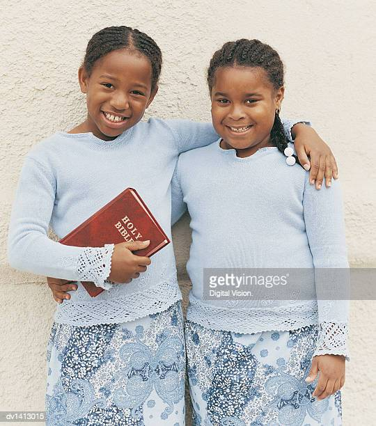 portrait of a young girl holding a bible with her arm around another smiling, young girl - free bible image stock pictures, royalty-free photos & images