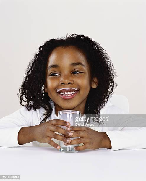 Portrait of a Young Girl Holding a Glass of Milk, Looking Sideways and Laughing, Milk on Her Top Lip