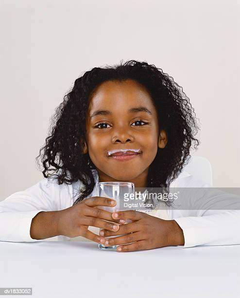 Portrait of a Young Girl Holding a Glass of Milk, Milk on Her Top Lip