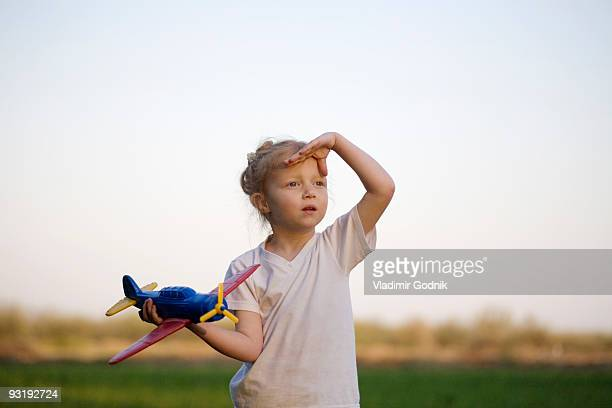 A portrait of a young girl holding a toy airplane and shielding her eyes, outdoors