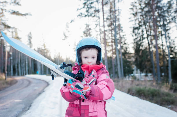 portrait of a young girl holding cross country skis in Sweden