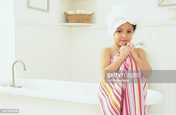 Portrait of a Young Girl in a Bathroom Wrapped in Towels Standing in Front of a Bath